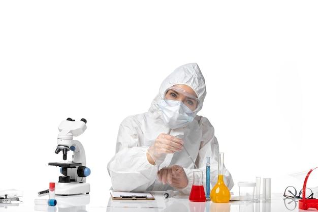 Vooraanzicht jonge vrouwelijke arts in wit beschermend pak met masker vanwege covid werken met oplossingen op witte achtergrond pandemic splash virus covid