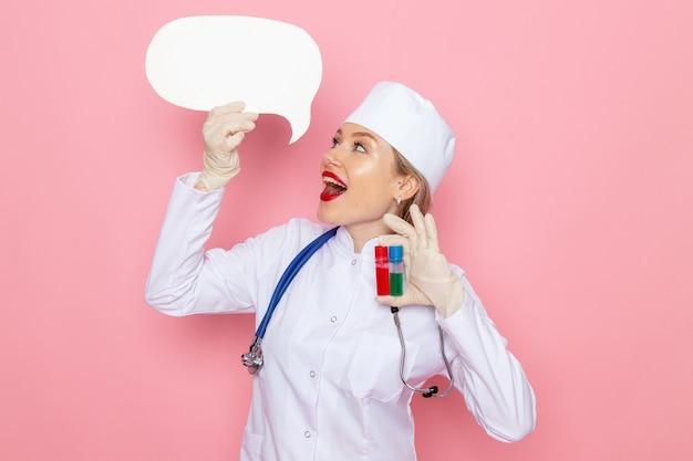 Vooraanzicht jonge vrouwelijke arts in wit medisch pak met blauwe stethoscoop met kolven en wit bord glimlachend op de roze ruimte geneeskunde medische ziekenhuis