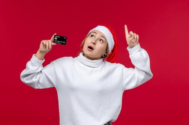Vooraanzicht jonge vrouwelijke bankkaart op lichte rode achtergrond