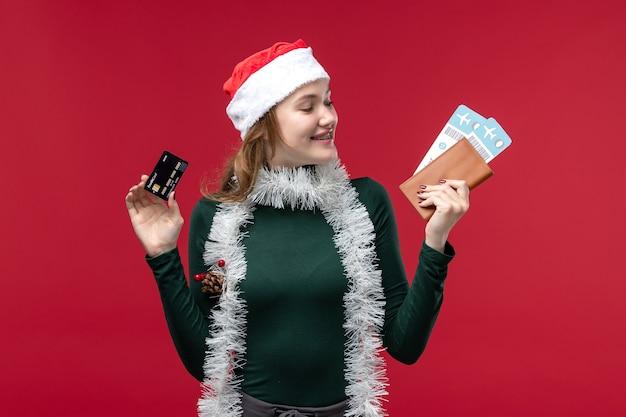 Vooraanzicht jonge vrouwelijke bankkaartkaartjes op rode achtergrond