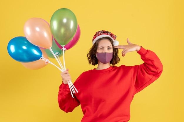 Vooraanzicht jonge vrouwelijke bedrijf ballonnen in steriel masker op gele vloer nieuwjaar kleur vrouw emotie feestviering