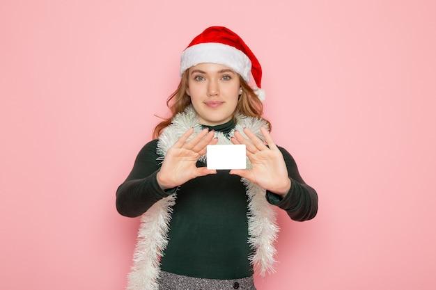Vooraanzicht jonge vrouwelijke bedrijf bankkaart op roze muur model vakantie kerst s
