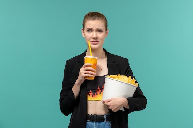 Vooraanzicht jonge vrouwelijke bedrijf chips drinken en kijken naar film op blauwe ondergrond