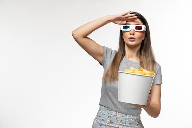 Vooraanzicht jonge vrouwelijke bedrijf chips en kijken naar film in d zonnebril op witte vloer eenzame films bioscoop vrouwelijke afstandsbediening