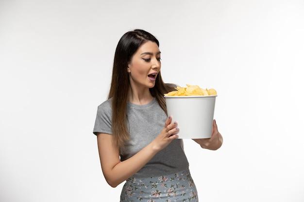 Vooraanzicht jonge vrouwelijke bedrijf chips en kijken naar film op wit oppervlak
