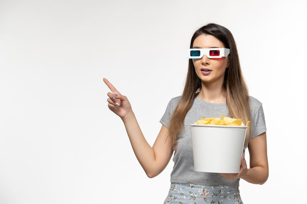 Vooraanzicht jonge vrouwelijke bedrijf chips tijdens het kijken naar film in d zonnebril op witte vloer film bioscoop eenzame vrouwelijke afstandsbediening
