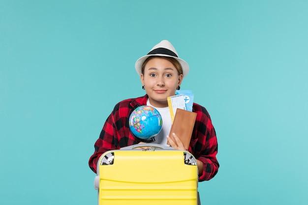 Vooraanzicht jonge vrouwelijke bedrijf kaartjes en globe op blauwe vloer reis reis vakantie reis vrouw