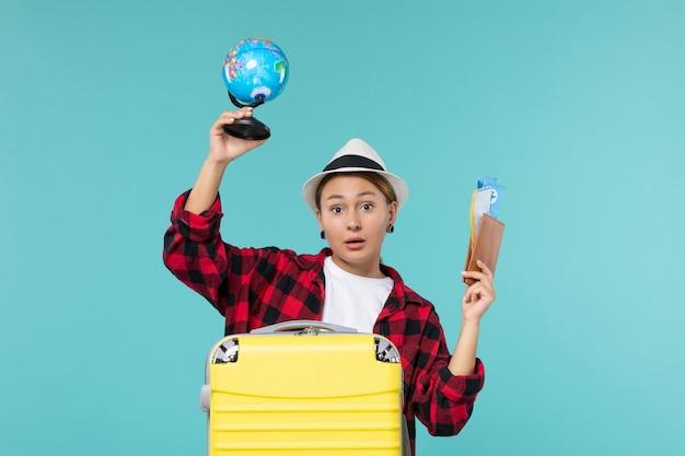 Vooraanzicht jonge vrouwelijke bedrijf kaartjes en globe op de blauwe ruimte