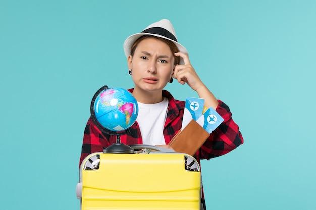 Vooraanzicht jonge vrouwelijke bedrijf kaartjes op de lichtblauwe ruimte