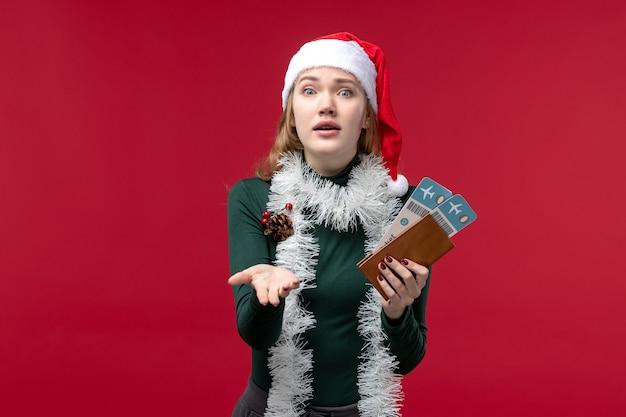 Vooraanzicht jonge vrouwelijke bedrijf kaartjes op rode achtergrond