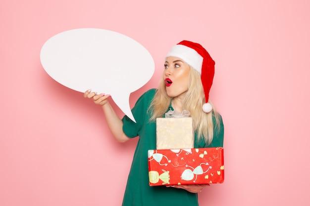 Vooraanzicht jonge vrouwelijke bedrijf kerstcadeautjes en wit bord op roze muur vrouw cadeau sneeuw kleurenfoto nieuwjaarsvakantie