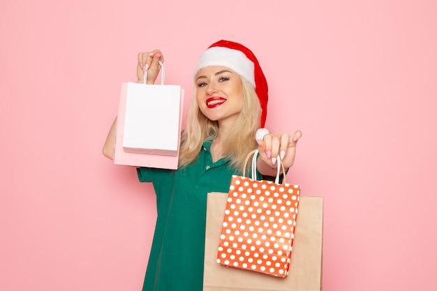 Vooraanzicht jonge vrouwelijke bedrijf kerstcadeautjes in pakketten op de roze muur xmas foto model nieuwjaarsvakantie