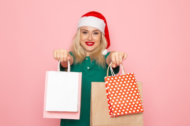 Vooraanzicht jonge vrouwelijke bedrijf kerstcadeautjes in pakketten op roze muur fotomodel nieuwjaarsvakantie