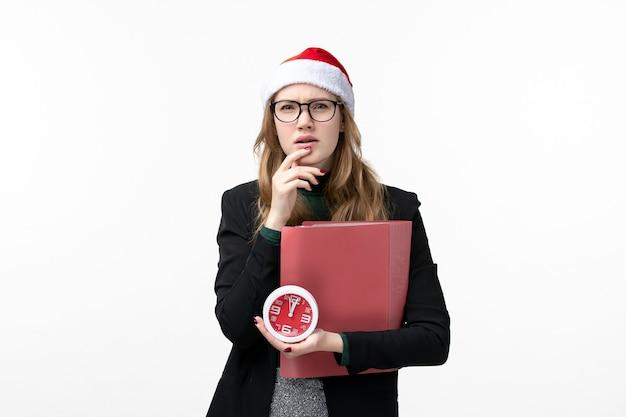 Vooraanzicht jonge vrouwelijke bedrijf klok en bestanden op witte muur boeken les college