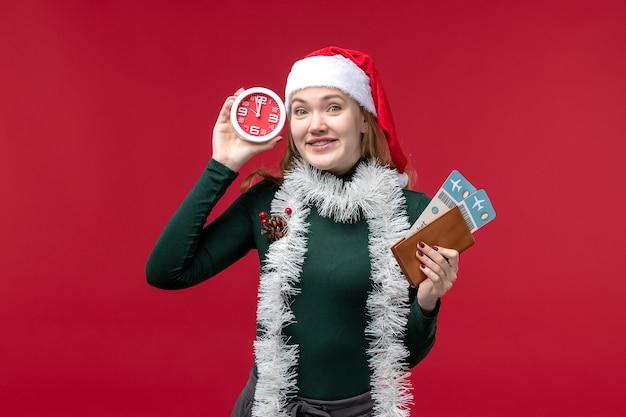 Vooraanzicht jonge vrouwelijke bedrijf klok en kaartjes op rode achtergrond