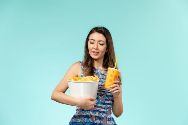 Vooraanzicht jonge vrouwelijke bedrijf mand met chips en drankje op blauw bureau