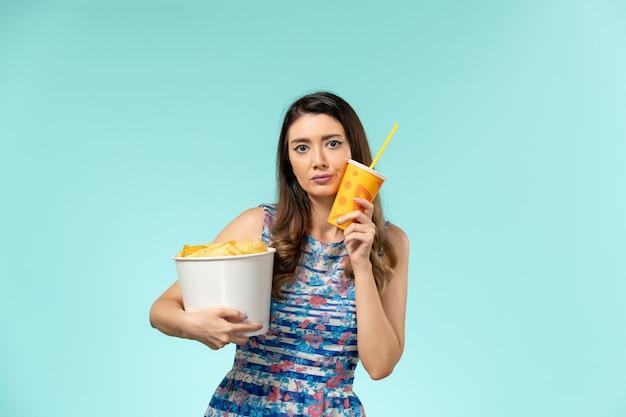Vooraanzicht jonge vrouwelijke bedrijf mand met chips en drankje op het blauwe oppervlak