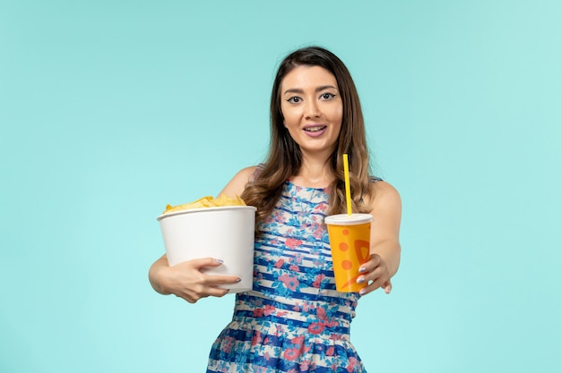 Vooraanzicht jonge vrouwelijke bedrijf mand met chips en drankje op lichtblauwe ondergrond