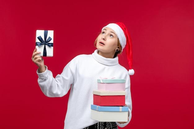 Vooraanzicht jonge vrouwelijke bedrijf nieuwjaar presenteert op rode achtergrond