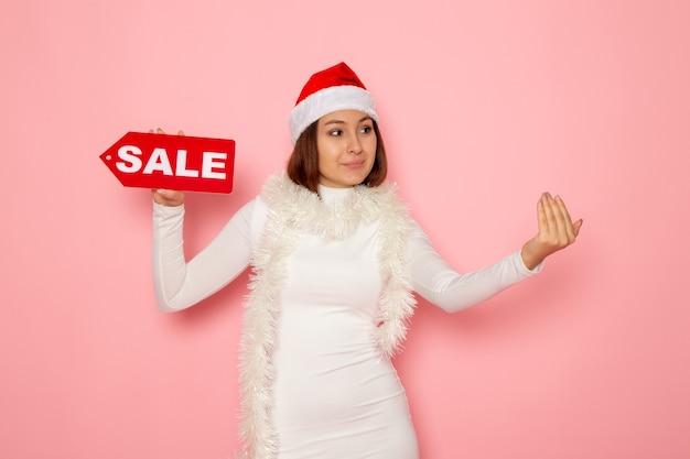 Vooraanzicht jonge vrouwelijke bedrijf verkoop geschreven figuur op roze muur kleur kerst nieuwjaar vakantie mode sneeuw