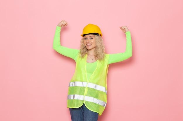Vooraanzicht jonge vrouwelijke bouwer in groen bouwpakhelm glimlachend en buigend op het roze bouwwerk van de ruimtearchitectuur