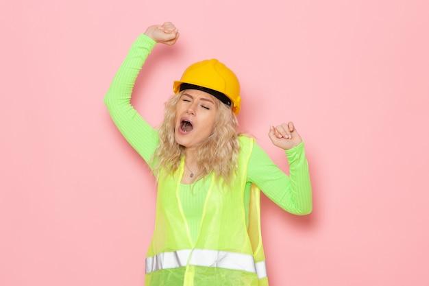 Vooraanzicht jonge vrouwelijke bouwer in groene bouw pak helm geeuwen op de roze ruimte architectuur bouwwerk dame baan