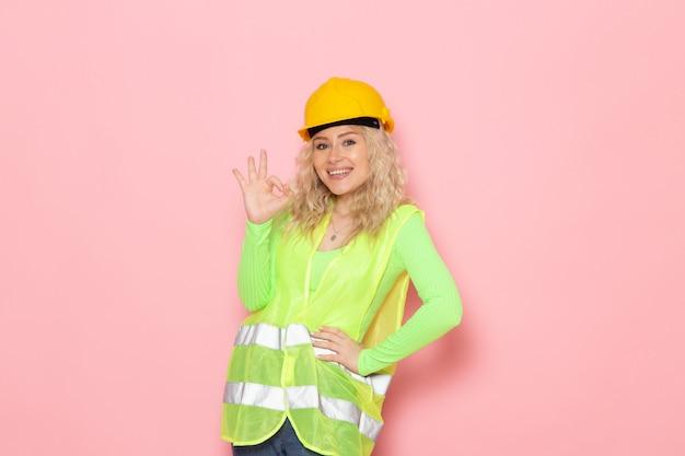 Vooraanzicht jonge vrouwelijke bouwer in groene bouw pak helm glimlachend en poseren op de roze ruimte architectuur bouwwerk dame