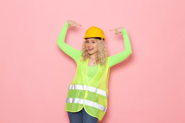 Vooraanzicht jonge vrouwelijke bouwer in groene bouw pak helm glimlachend en poseren op de roze ruimte