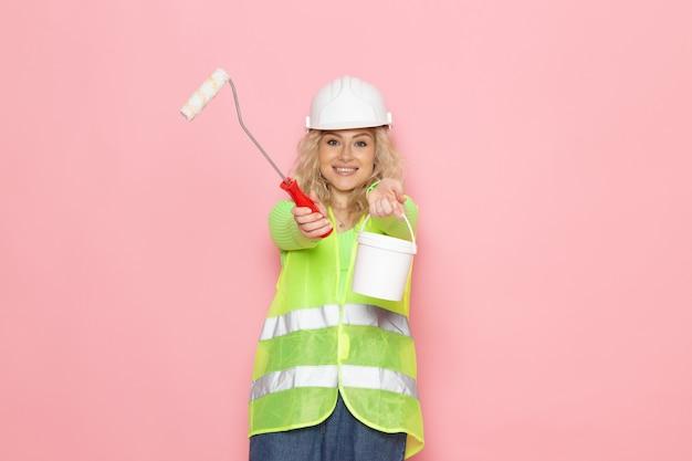 Vooraanzicht jonge vrouwelijke bouwer in groene bouw pak helm met verf en penseel op de roze ruimte