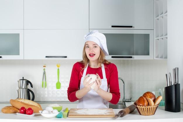 Vooraanzicht jonge vrouwelijke chef-kok in koksmuts en schort die deeg in de keuken ophouden