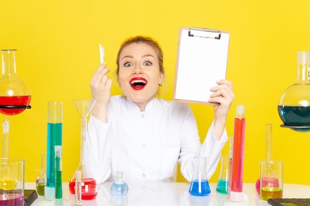 Vooraanzicht jonge vrouwelijke chemicus die in wit pak met verschillende oplossingen zit die blocnote houdt en op de gele wetenschap van de ruimtechemie glimlacht