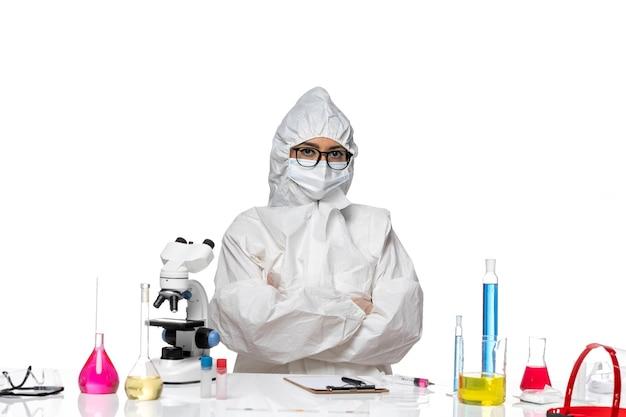 Vooraanzicht jonge vrouwelijke chemicus in speciaal beschermend pak gewoon zittend met oplossingen op witte achtergrond virus lab covid chemie gezondheid