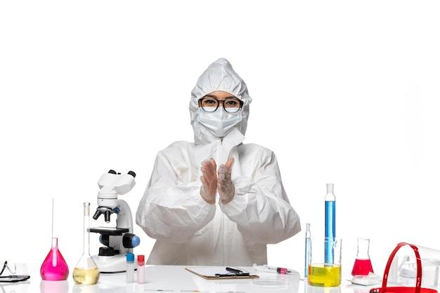 Vooraanzicht jonge vrouwelijke chemicus in speciaal beschermend pak glimlachend en klappen op wit bureau virus lab covid gezondheid chemie