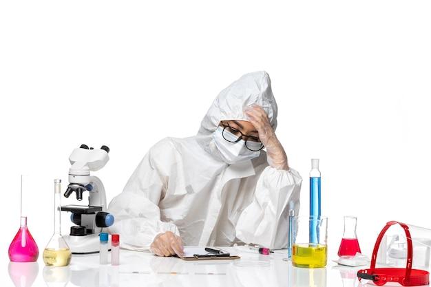 Vooraanzicht jonge vrouwelijke chemicus in speciaal beschermend pak moe op witte achtergrond lab covid chemie virus gezondheid