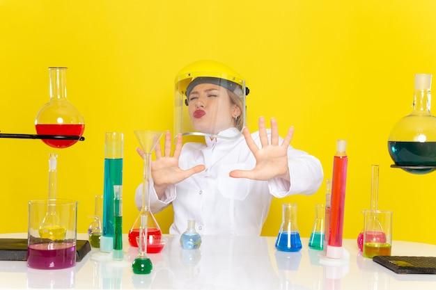 Vooraanzicht jonge vrouwelijke chemicus in wit pak met ed-oplossingen die een helm dragen die ontevreden is over de gele ruimtechemie wetenschap s