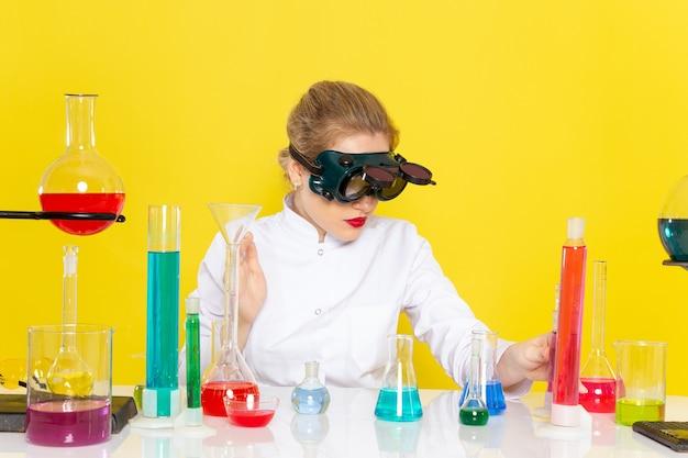 Vooraanzicht jonge vrouwelijke chemicus in wit pak met ed-oplossingen die met hen werken en op de gele ruimtechemie zitten