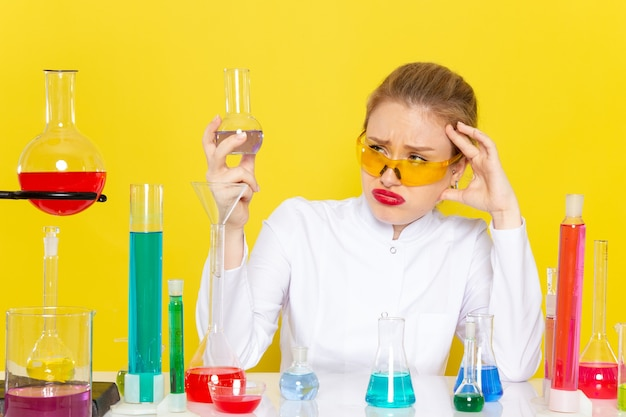 Vooraanzicht jonge vrouwelijke chemicus in wit pak met ed-oplossingen die met hen werken, zittend op de gele wetenschap van de ruimtechemie