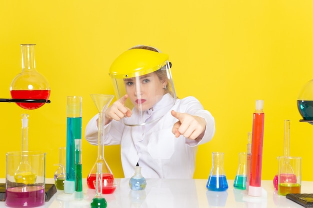 Vooraanzicht jonge vrouwelijke chemicus in wit pak met ed-oplossingen dragen helm poseren op de gele ruimte chemie wetenschap s
