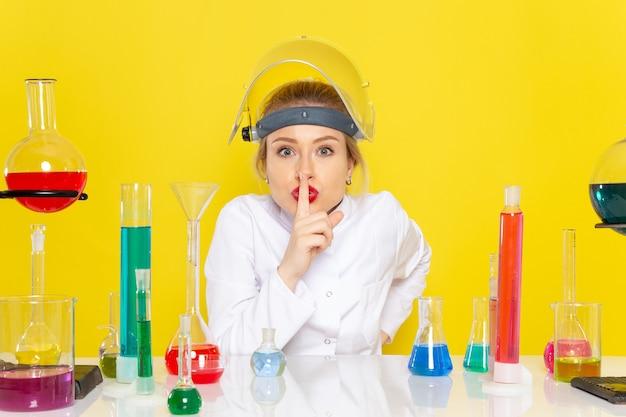 Vooraanzicht jonge vrouwelijke chemicus in wit pak met ed-oplossingen met helm op haar hoofd stilte teken tonen op de gele ruimte chemie wetenschap s