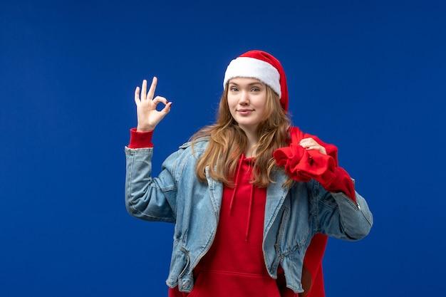 Vooraanzicht jonge vrouwelijke draagtas vol cadeautjes op blauwe ruimte