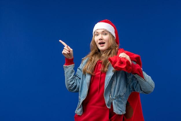 Vooraanzicht jonge vrouwelijke draagtas vol cadeautjes op lichtblauwe ruimte