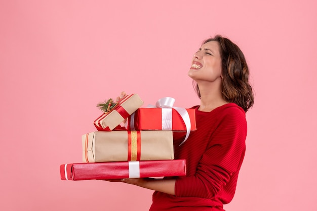Vooraanzicht jonge vrouwelijke dragende kerstcadeautjes op het roze