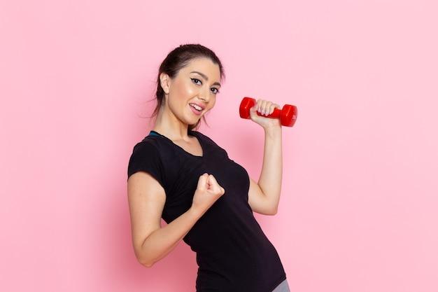 Vooraanzicht jonge vrouwelijke halters met opgetogen uitdrukking op lichtroze muur atleet sport oefening gezondheidstraining