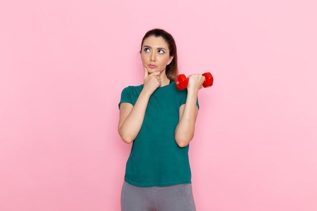 Vooraanzicht jonge vrouwelijke halters op de roze muur atleet sport oefening gezondheid trainingen