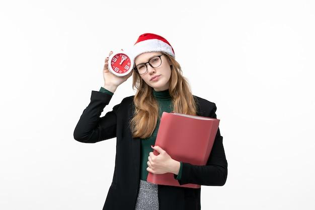 Vooraanzicht jonge vrouwelijke holdingsdossiers en klok op wit kerstmisboek van het bureaunieuwjaar