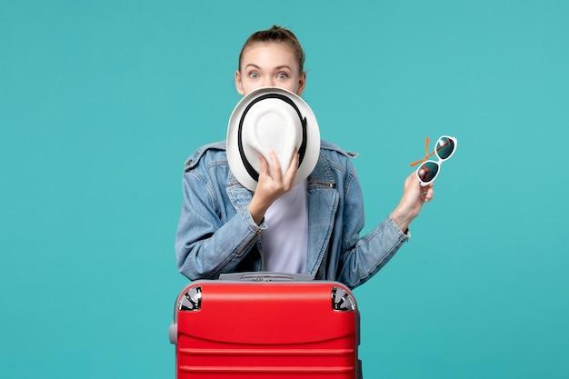 Vooraanzicht jonge vrouwelijke holdingszonnebril en hoed die voor vakantie op blauwe ruimte voorbereidingen treffen