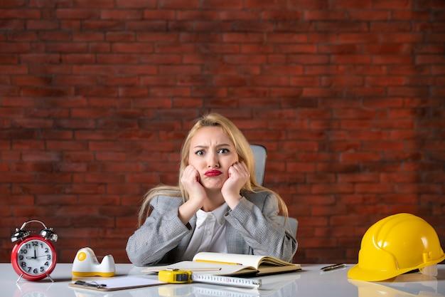 Vooraanzicht jonge vrouwelijke ingenieur zittend op kantoor