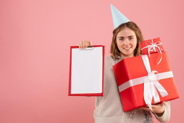 Vooraanzicht jonge vrouwelijke kerstcadeautjes en notitie