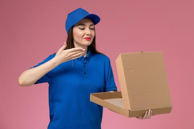 Vooraanzicht jonge vrouwelijke koerier in blauw uniform en cape die lege voedseldoos houden die het op roze muur ruiken