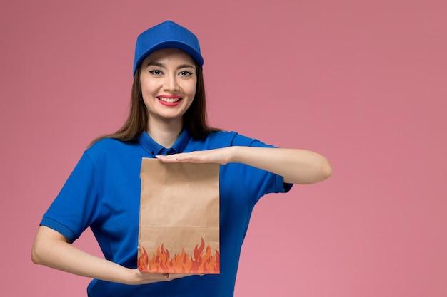 Vooraanzicht jonge vrouwelijke koerier in blauw uniform en cape met papier voedselpakket en glimlachend op lichtroze bureau